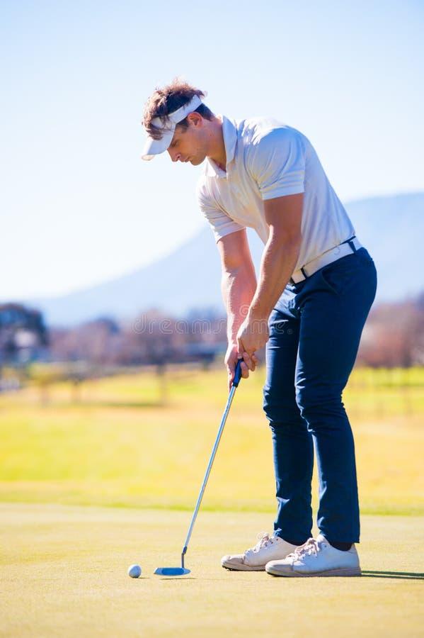 Mening van een golfspeler die zijn schot plannen aan de speld stock fotografie