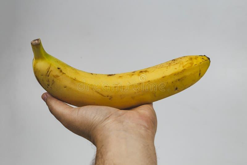 mening van een hand die een banaan houden tegen witte achtergrond stock foto's