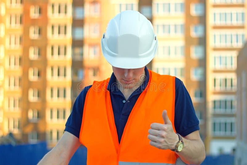 Mening van een Ingenieur en arbeiders het letten op blauwdruk op bouwwerf royalty-vrije stock afbeelding