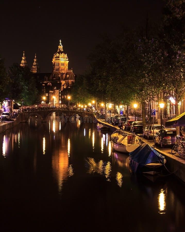 Mening van een kerk en een kanaal in Amsterdam, Nederland bij nacht De Basiliek van Heilige Nicholas Sint-Nicolaasbasiliek met r stock afbeeldingen