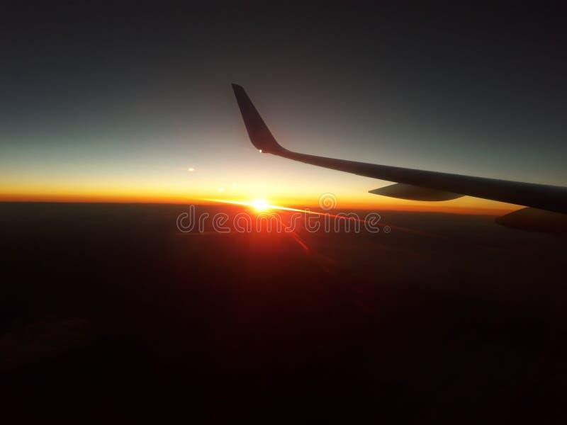Mening van een vliegtuigvenster op een zonsondergang, stralen van de zon bij een daling stock afbeelding
