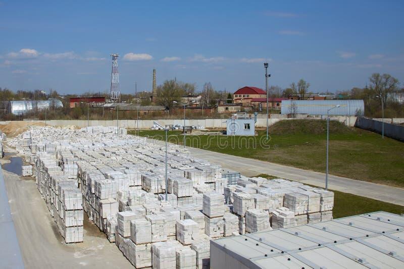Mening van fabrieksinstallatie die gesteriliseerd met autoclaaf gelucht beton produceren Vele pakketten van blokken op pallets ze stock foto's
