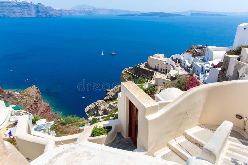 Mening van Fira-stad - Santorini-eiland, Kreta, Griekenland. Witte concrete trappen die neer tot mooie baai leiden stock fotografie