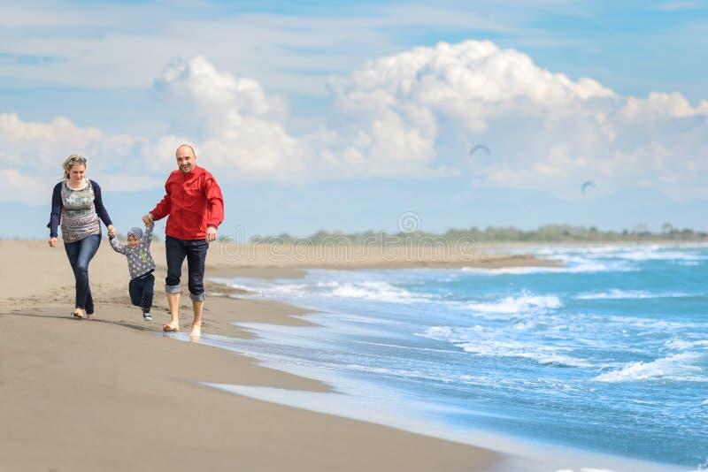 Mening van gelukkige jonge familie die pret op het strand hebben stock afbeeldingen