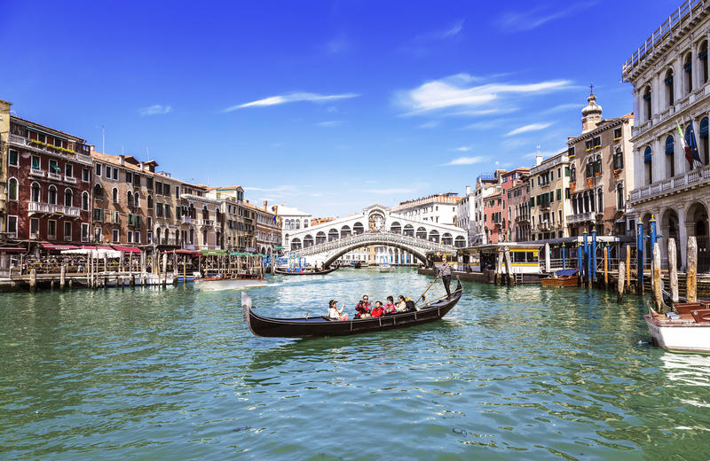 Mening van Grand Canal, de Rialto-Brug en de gondel met toeristen Venetië stock foto