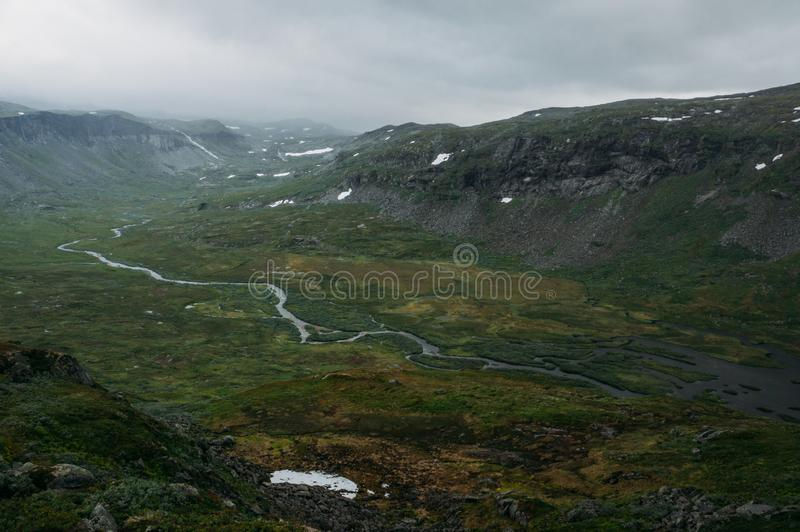 mening van groen die grasgebied met rivierstroom door rotsachtige klippen, Noorwegen, Hardangervidda wordt omringd stock fotografie