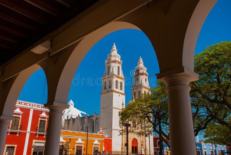 Mening van het belangrijkste Park door de boog van het bibliotheekgebouw in Campeche, Mexico Op de achtergrond is de kathedraal d stock afbeelding