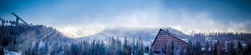 Mening van het de winter de toneelpanorama van berg met een hotel en schansspringenplatform stock foto