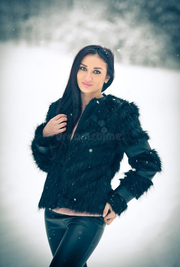Mening van het gelukkige donkerbruine meisje spelen met sneeuw in de winterlandschap Mooi jong wijfje op de winterachtergrond Aan royalty-vrije stock fotografie
