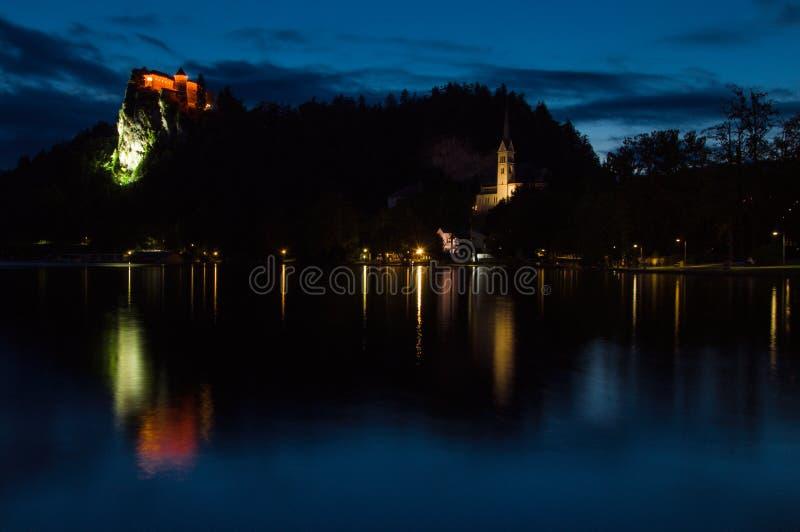 Mening van het meer en het Afgetapte Kasteel, zonsondergang, bezinning van het kasteel in het meer, Slovenië royalty-vrije stock foto