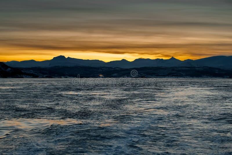 Mening van het overzees aan de het plaatsen zon achter de bergen Donkere tijd van dag stock fotografie