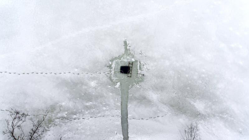 Mening van hierboven bij geregeld ijs-gat met weg van kust en menselijke voetafdrukken op ijs van de wintermeer Hoogste mening stock afbeeldingen