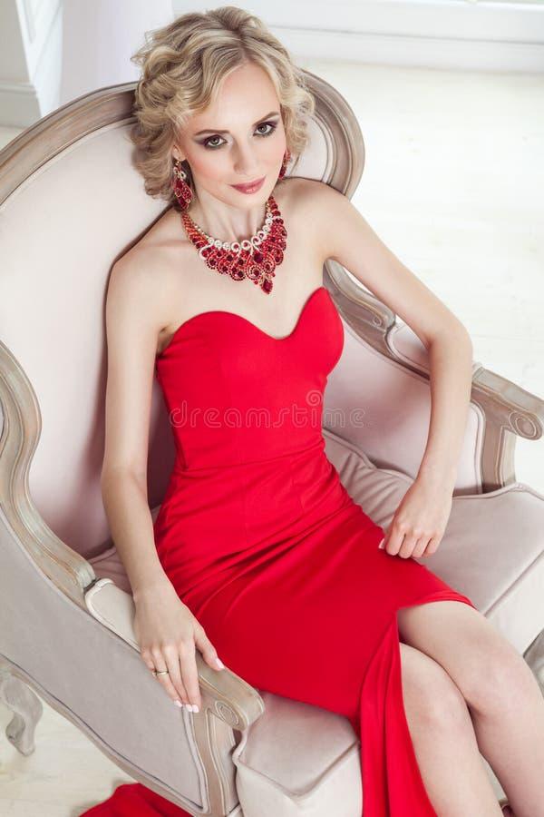 Mening van hierboven Elegantievrouw in rode kleding, die op stoel situeren royalty-vrije stock fotografie