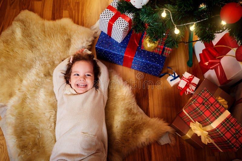 Mening van hierboven Het meisje in Kerstmis ligt op de vloer in F stock afbeeldingen