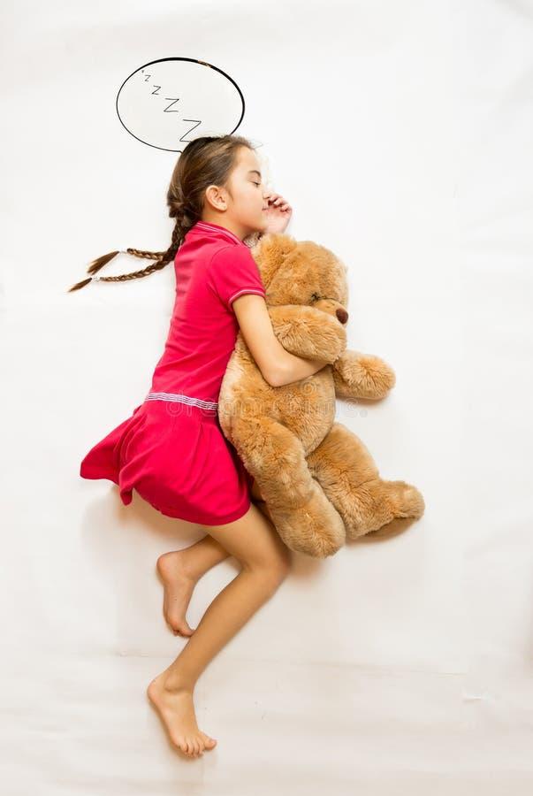 Mening van hoogste mening die van het dromen van meisje op grote teddybeer liggen royalty-vrije stock fotografie