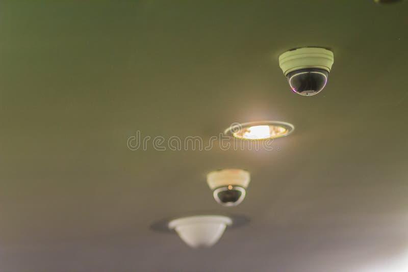 Mening van kabeltelevisie-veiligheids digitale camera op plafond met verlichtingsla stock afbeelding
