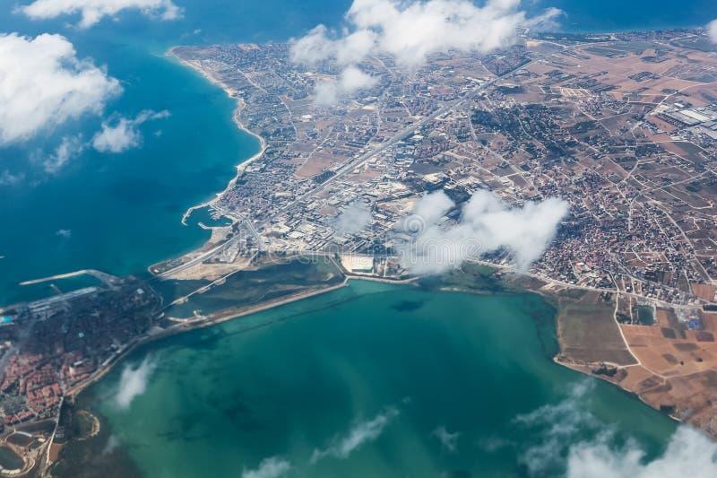 Mening van land van vliegtuigen, blauwe overzees, boven de wolken stock fotografie