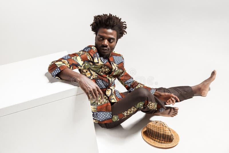 Mening van mens van abow de jonge volwassen afro, die op vloer zitten royalty-vrije stock afbeeldingen