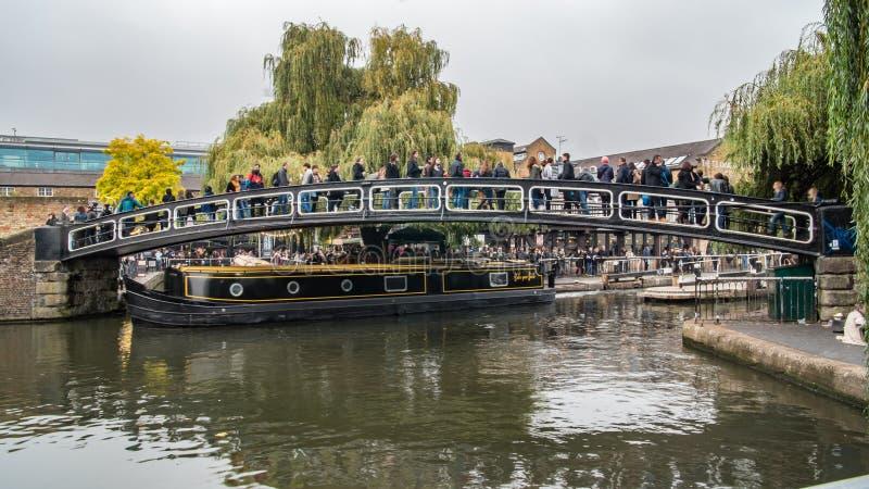 Mening van mensen die een brug over het kanaal kruisen bij de stad van Camden bij de ingang van de Slotmarkt in Londen royalty-vrije stock afbeeldingen