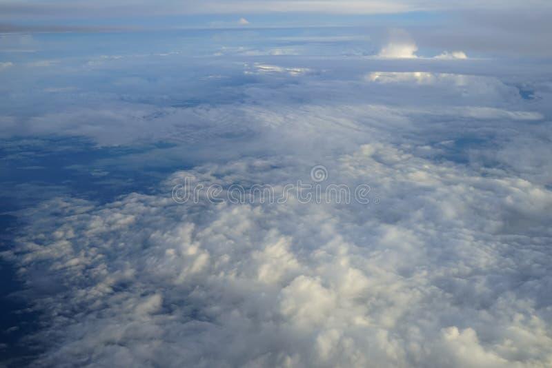 Mening van mooie abstracte zachte witte cloudscape met schaduwen van blauwe hemelachtergrond van vliegend vliegtuigvenster royalty-vrije stock afbeeldingen