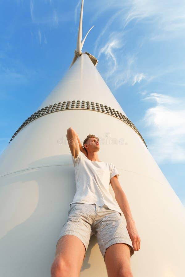 Mening van onderaan van een koele jonge kerel Tiener die op de elektrische windmolen leunen Modieuze mannelijk op een blauwe heme royalty-vrije stock foto