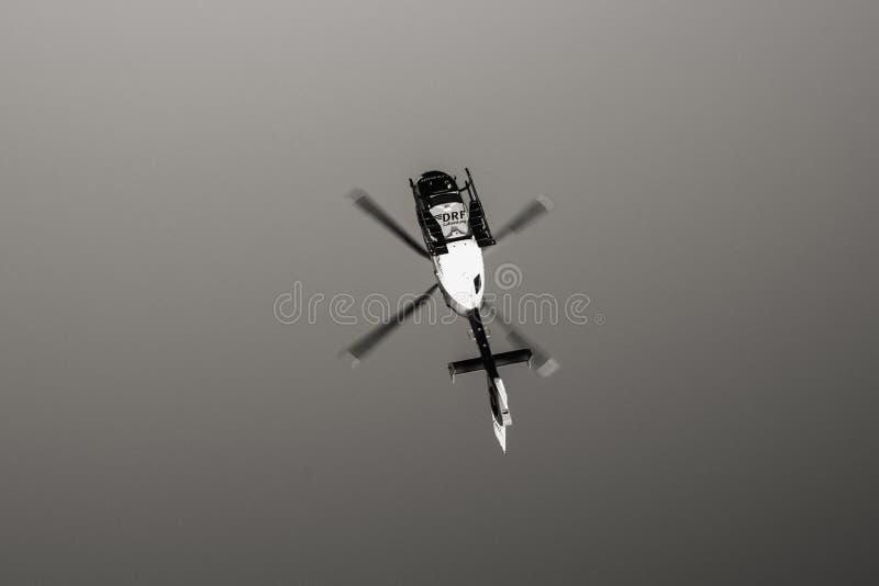 Mening van onderaan van reddingshelikopter DRF die Luftrettung in c vliegen stock foto's