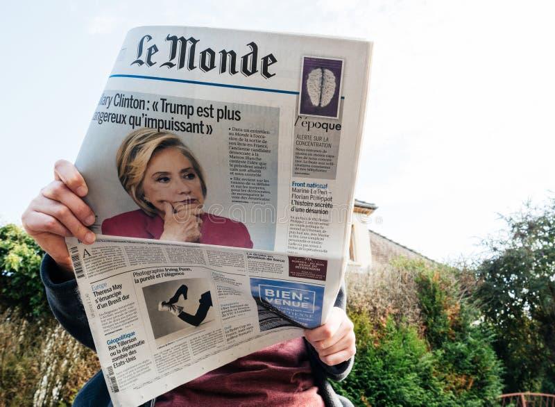 Mening van onderaan van vrouw die recentste krant Le Monde met portret van Hillary Clinton lezen royalty-vrije stock foto