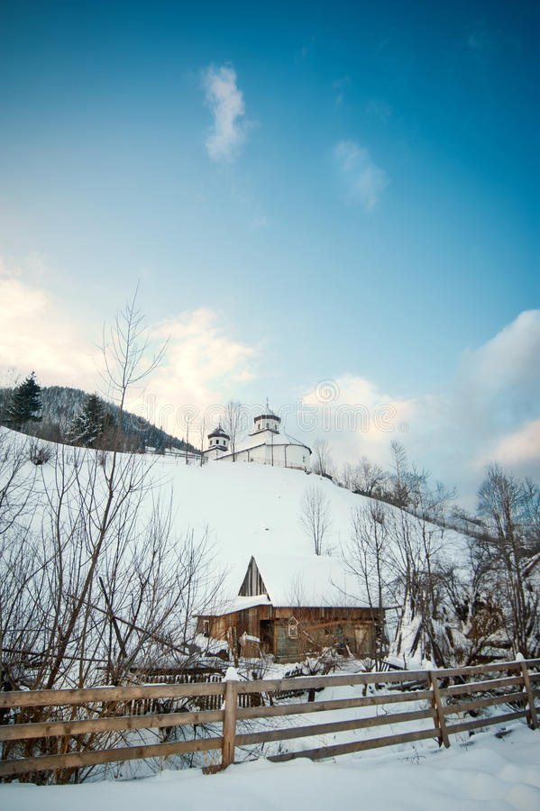 Mening van Roemeense kleine die kerk op heuvel met sneeuw wordt behandeld De winterlandschap met orthodoxe kerk over blauwe hemel royalty-vrije stock foto's