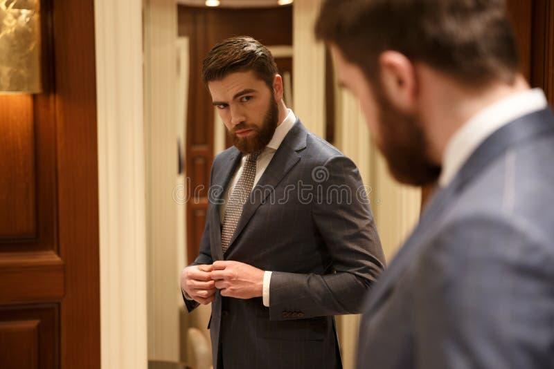 Mening van rug van de knappe mens die de spiegel bekijken stock afbeelding