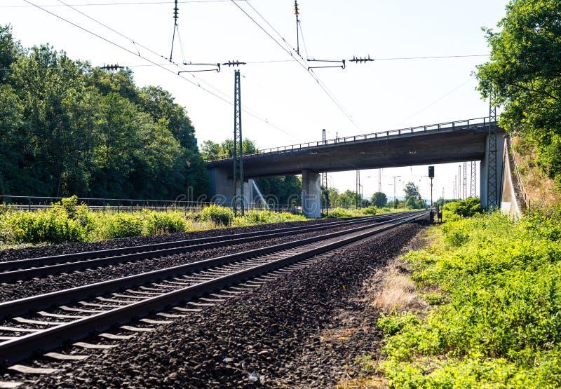 Mening van spoorwegsporen op een de zomer zonnige dag met zichtbare viaduct en hoogspanningslijnen royalty-vrije stock foto