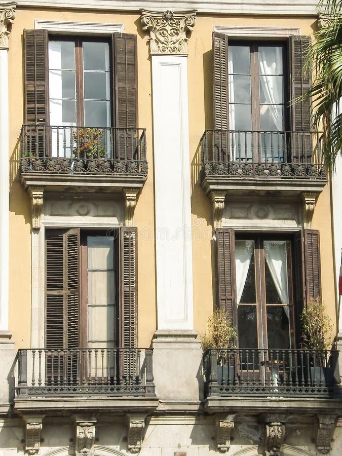 Mening van vier vensters met balconys op een muurachtergrond royalty-vrije stock afbeeldingen