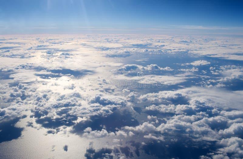 Mening van vliegtuigvenster Wolken hierboven - waterspiegel atmosfeerconcept Blauwe achtergrond Broeikaseffect bewolkte dag royalty-vrije stock fotografie