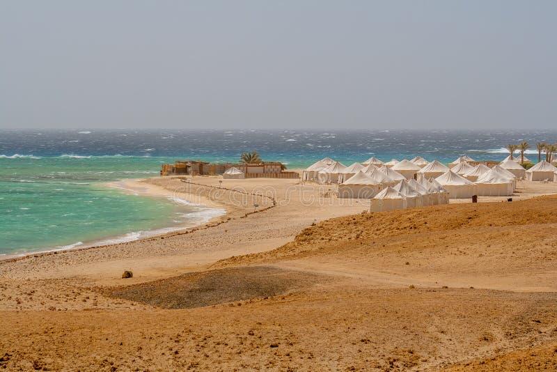Mening van Wilde Golven die over Coral Reef en Bedouin Tenten in Wind op Strand in Marsa Alam verpletteren royalty-vrije stock fotografie