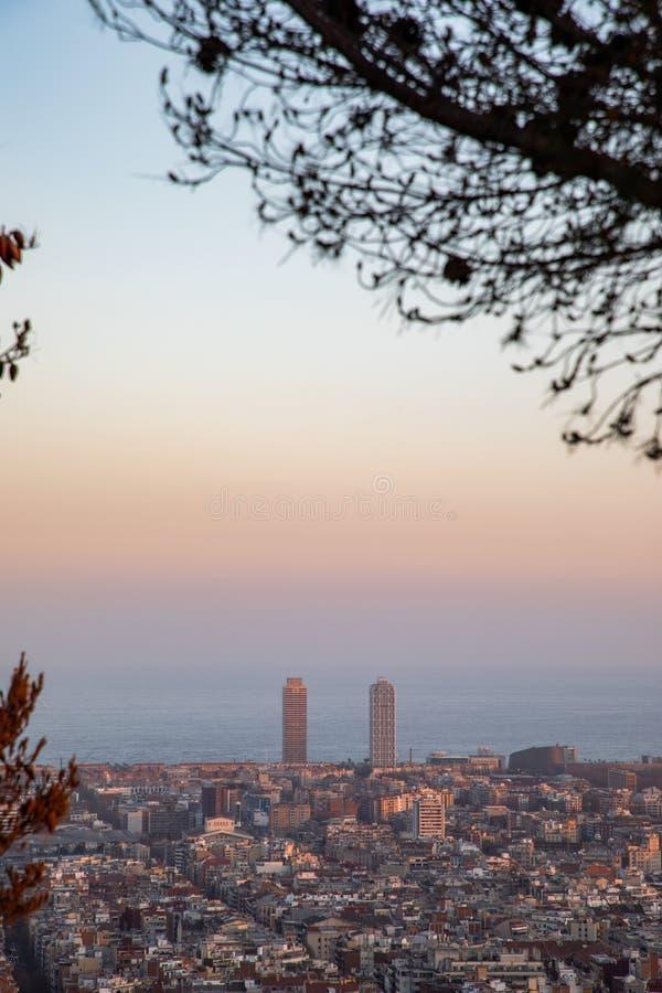 Meningen van de stad van Barcelona tijdens zonsondergang met boomkader stock foto's