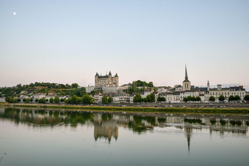 Meningen van de stad van Saumur van riverbank bij schemer, met het kasteel op de achtergrond De Vallei van de Loire, Frankrijk royalty-vrije stock foto's