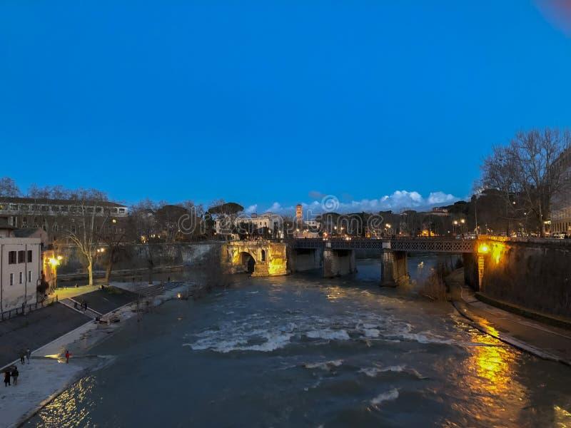 Meningen van een zonsondergang op de Tiber-rivier en de onherkenbare mensen die langs zijn kust lopen stock fotografie