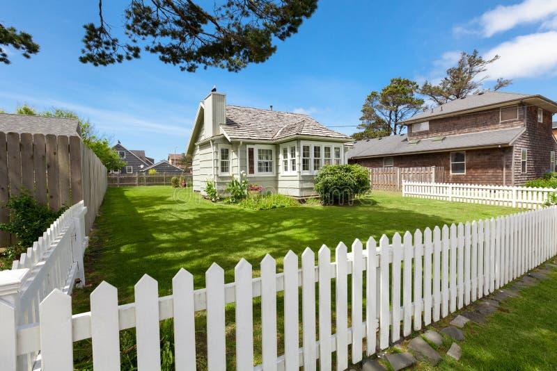 Meningsplattelandshuisje In de voorsteden, gazon met groen gras, Kanonstrand, Oregon, de V.S. royalty-vrije stock fotografie