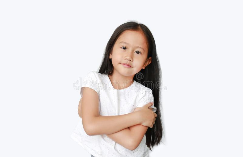 Menininha Asiática confiante com expressão através do braço e câmera parecida isolada em fundo branco Crianças animadas imagens de stock royalty free
