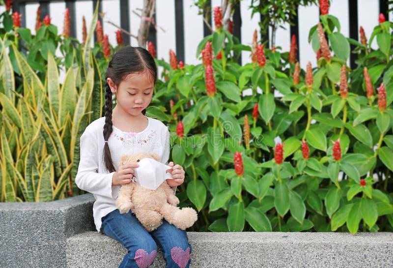 Menininha asiática usando máscara para a boneca de ursinho para proteger o cúvio-19 do coronavírus e a poluição do ar na cidade d fotografia de stock royalty free