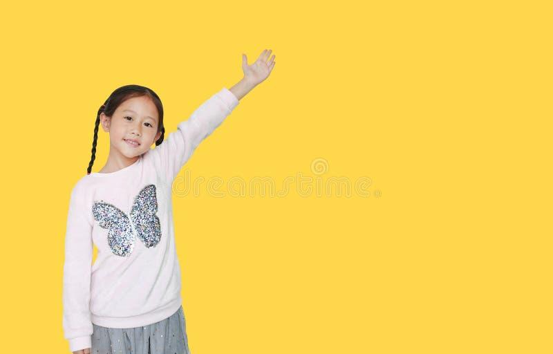 Menininha parada e pontos levantados apresentam algo isolado em fundo amarelo com espaço de cópia Escola asiática em fotografia de stock