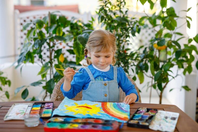 Menininha pintando arco-íris e sol com aquarelas durante a pandemia de quarentena do coronavírus Crianças fotografia de stock