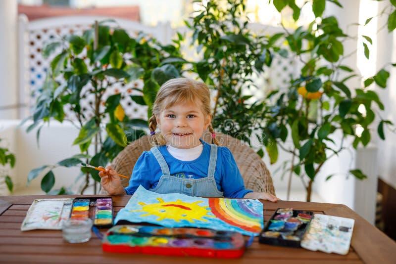 Menininha pintando arco-íris e sol com aquarelas durante a pandemia de quarentena do coronavírus Crianças foto de stock royalty free
