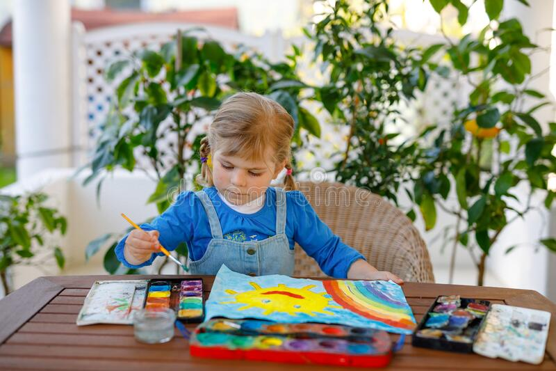 Menininha pintando arco-íris e sol com aquarelas durante a pandemia de quarentena do coronavírus Crianças fotografia de stock royalty free