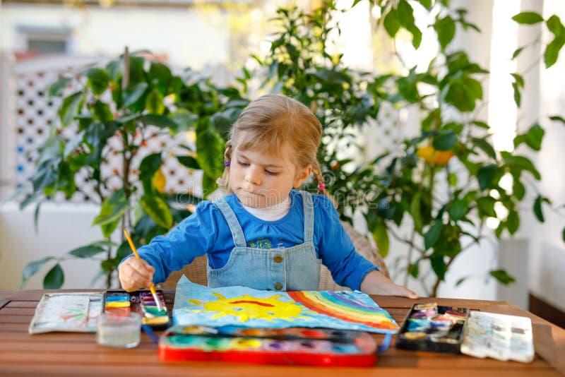 Menininha pintando arco-íris e sol com aquarelas durante a pandemia de quarentena do coronavírus Crianças foto de stock