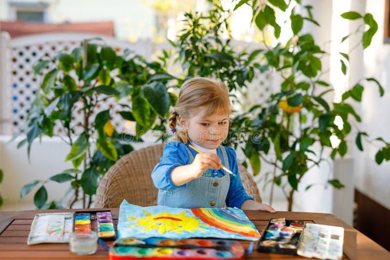 Menininha pintando arco-íris e sol com aquarelas durante a pandemia de quarentena do coronavírus Crianças fotos de stock royalty free