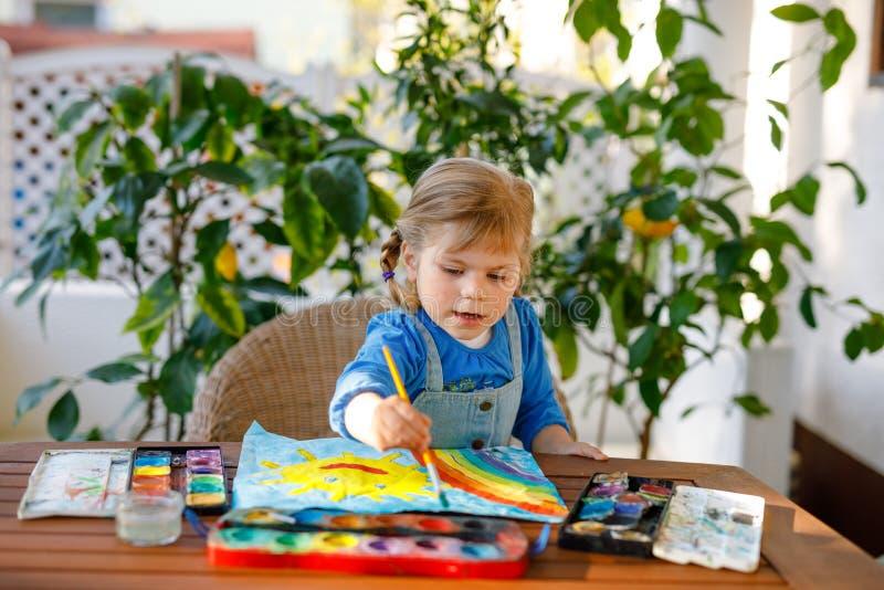 Menininha pintando arco-íris e sol com aquarelas durante a pandemia de quarentena do coronavírus Crianças imagem de stock royalty free