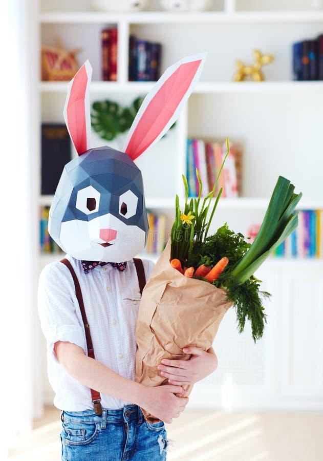 Menino à moda bonito, na máscara poligonal do coelho de easter com um saco completamente de verdes frescos da mola fotos de stock royalty free