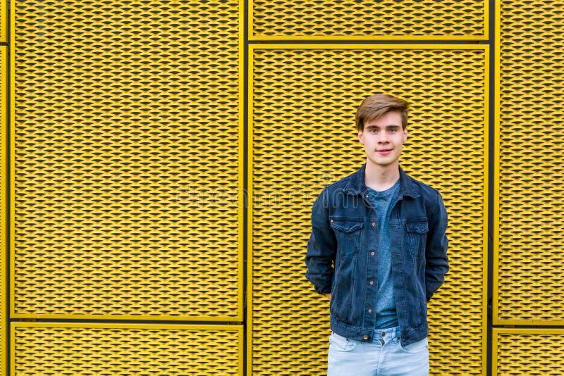 Menino adolescente à moda sobre o copyspace amarelo industrial do fundo imagem de stock royalty free
