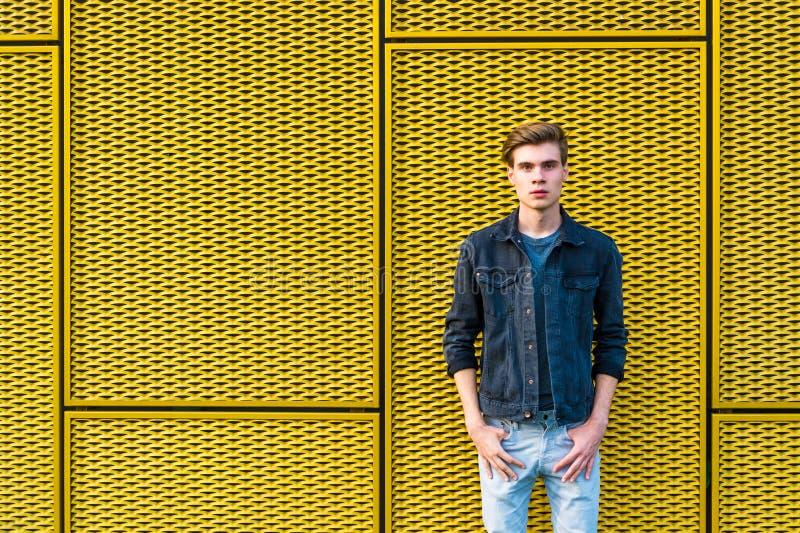 Menino adolescente à moda sobre o fundo amarelo industrial fotografia de stock