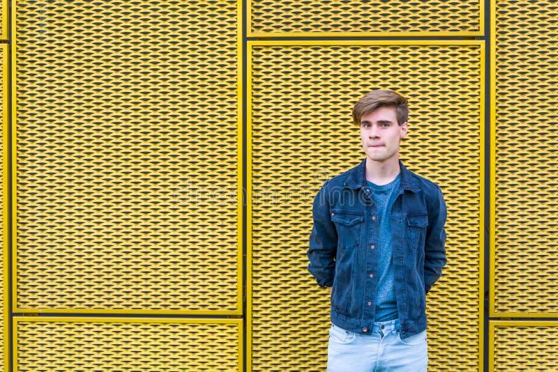 Menino adolescente à moda sobre o pensamento amarelo industrial do fundo imagem de stock royalty free
